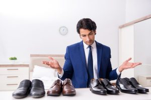 Man Deciding Between Pairs of Shoes