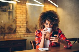 Woman in Cafe Reading on Smartphone | Global Dynamic Technology, LLC